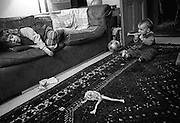 """A three and half year-old girl takes a mid-afternoon nap on the sofa in her South London home. While she sleeps her one year-old brother has taken the opportunity to take a leg from her doll and bite it with his new teeth. He sits on the rug and watches her expecting her to awake at any moment. From a personal documentary project entitled """"Next of Kin"""" about the photographer's two children's early years spent in parallel universes. Model released."""
