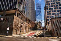 A pedestrian quietly crosses Columbia Street in the eery silence of Downtown Seattle. (April 4, 2020).