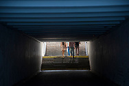 People walk up steps into sunlight after using a pedestrian tunnel to cross beneath a highway beside the Dnieper River in Kiev, Ukraine