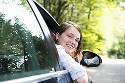 Young woman looking out of car window and smiling, Bavaria, Germany