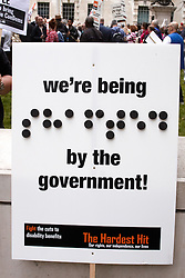 © licensed to London News Pictures. LONDON, UK  11/05/2011. Sign partly in Braille at the Hardest Hit march. The Braille reads shafted. Thousands of disabled people march past Parliament to protest against cuts to the support offered to the physically and mentally handicapped in particular the disability living allowance (DLA). Please see special instructions for usage rates. Photo credit should read CLIFF HIDE/LNP