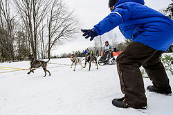 Jules Struyzna of Middlebury, VT is guided around a turn by a course marshal during the final day of the Worlds Championship Sled Dog Derby in Laconia on Sunday February 16, 2020.(Alan MacRae for the Laconia Daily Sun)