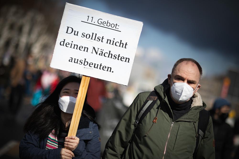 """Mehrere hundert Menschen protestieren am europaweiten """"Housing Action Day 2021"""" in Berlin gegen Verdrängung und für ein Recht auf Wohnen. Die Demonstranten protestieren gegen steigende Mieten und Verdrängung und fordern ein Umwandlungsverbot von Miet- in Eigentumswohnungen, Mietsenkungen und bezahlbaren Wohnraum. Demonstrantin mit Schild: 11. Gebot: Du sollst nicht deinen Nächsten ausbeuten. Berlin, Deutschland, 27.03.2021.<br /> <br /> [© Christian Mang - Veroeffentlichung nur gg. Honorar (zzgl. MwSt.), Urhebervermerk und Beleg. Nur für redaktionelle Nutzung - Publication only with licence fee payment, copyright notice and voucher copy. For editorial use only - No model release. No property release. Kontakt: mail@christianmang.com.]"""