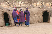 Africa, Tanzania, Maasai an ethnic group of semi-nomadic people. Woman by the mud huts