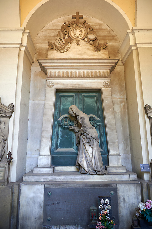 Picture and image of the stone sculpture of a  mourning widow who is bringing a crown and knocking on a sepulcher's bronze door, which holds the bas relief of an hourglass, a classic symbol of the passing of time. This theme of the sorrowful survivor in front of the sepulcher's door comes from the Monument dedicated to Maria Christina, Duchess of Teschen, Maria Theresa of Austria's daughter, a neoclassical sculpture. In this version the widow is wearing fashionable clothes, which have been accurately represented, and her openwork shawl. Sculptor G. B. Cevasco 1875. The monumental tombs of the Staglieno Monumental Cemetery, Genoa, Italy .<br /> <br /> Visit our ITALY PHOTO COLLECTION for more   photos of Italy to download or buy as prints https://funkystock.photoshelter.com/gallery-collection/2b-Pictures-Images-of-Italy-Photos-of-Italian-Historic-Landmark-Sites/C0000qxA2zGFjd_k<br /> If you prefer to buy from our ALAMY PHOTO LIBRARY  Collection visit : https://www.alamy.com/portfolio/paul-williams-funkystock/camposanto-di-staglieno-cemetery-genoa.html