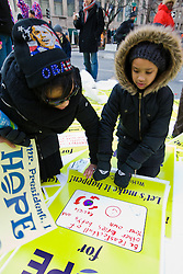 Child and mother writing hopes on placards during demonstration by hopeforchange.org at Presidential Inauguration of Barack Obama, Washington D.C., USA.
