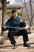 Man plays an Erhu instrument using a bow, in the park by the City Wall, Xian, China