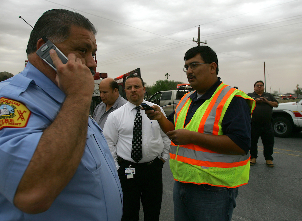 """San Isidro, TX - 18 Mar 2008 -.Incident commander Domingo """"Mingo"""" Hinojosa (right) plans an attack on the fire as Mission Fire department chief Ricardo Saldaña gives an order by phone on FM 755 outside San Isidro on Tuesday afternoon..Photo by Alex Jones / ajones@themonitor.com"""