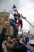 Brexit protesters attempt to resue a fallng street lamp glass bowl as winds force a flag to pull it from its base in Westminster on 4th April 2019 in London, England, United Kingdom. With just over two weeks until the UK is supposed to be leaving the European Union, the final result still hangs in the balance.