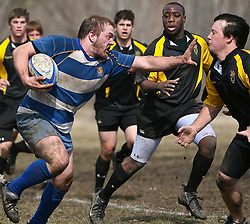 Bethel University rugby team member charges towards a Gustavus Adolphus College team member on a muddy afternoon game at Gustavus.