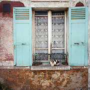 A typical old French house window and shutters with a curious cat in the French town of Gonesse, north of Paris.