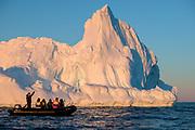 Evening with ecotourists and iceberg at Hydruga Rocks, Palmer Archipelago, Antarctica.