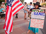 16 OCTOBER 2011 - PHOENIX, AZ: An Occupy Phoenix protester waves an American flag at passing cars during the protest in downtown Phoenix, AZ, Sunday. About 200 people continued the Occupy Phoenix protest in downtown Phoenix Sunday afternoon. The protest peaked Saturday afternoon at about 2,000 people. Nearly 50 people were arrested late Saturday night on misdemeanor trespassing charges when they tried to camp in a park near downtown and on Sunday the crowd dwindled to 200. Protesters hope to continue the protest through Monday by marching around downtown and picketing banks in the area.   PHOTO BY JACK KURTZ