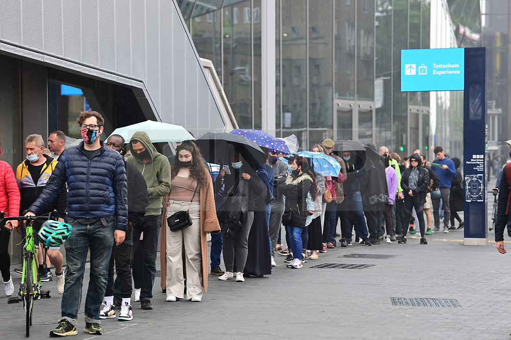 © Licensed to London News Pictures. 20/06/2021. London, UK. Members of the public queue at Tottenham Hotspur Stadium in north London where COVID-19 vaccines are being offered to all adults over the age of 18. Several sports stadiums across the capital are being used as mass vaccination centres over the weekend. Photo credit: Ben Cawthra/LNP