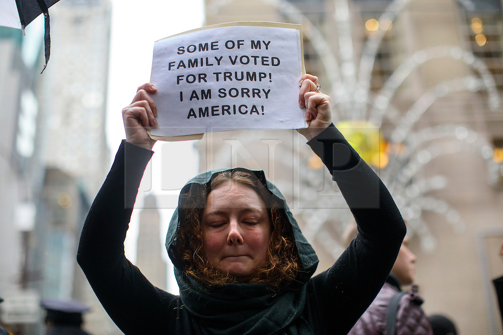 © Licensed to London News Pictures. 09/11/2016. New York CIty, USA. Anti-Trump campaigner holds a placard outside Trump Tower in New York City, on Wednesday, 9 November 2016 following the presidential election won by Donald Trump. Photo credit: Tolga Akmen/LNP