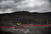 Hundreds of environmental activists stopping the open cast coal mine Ffos-y-Fran near Merthyr Tydfil, Wales from operating May 3rd 2016. Hundreds of activists dressed in red form a Red Line in the mine to symbolise the red line made in Paris at the COP21. The activists from Reclaim the Power wants the mine shut down and a moratorium on all future open coal mining in Wales. The group Reclaim the Power had set up camp near by and had over three days prepared the action and up to 300 activists all dressed in red went into the mine in the early morning. The activist were plit in three groups and carried various props signifying the red line in the sand, initially drawn in Paris at the COP21. The mine is one of the largest open cast coal mines in the UK and is run by Miller Argent who have to date extracted 5million tons of coal. The activists entered the mine unchallenged by any security or police and the protest went on peacefully till mid afternoon with no arrests made.  Open coal mining is hugely damaging to the local environment and  contributing to global climate change.