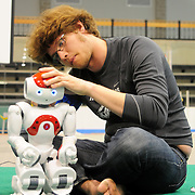 "May 2, 2009 -- BRUNSWICK, Maine. Bowdoin College Senior and ""Northern Bites""  team Captain Tucker Hermans fixes a faulty part in the mechanism of a Bowdoin robot at half time of a 2009 RoboCup U.S. Open match on Saturday afternoon on the campus. The competitors were tasked with creating software for two-legged robots which could independently play soccer with each other. ""Once we put them on the field, they are completely autonomous,""  said Bowdoin Professor of Computer Science and team advisor, Eric Chown, said. ""I'm extremely proud of every one on this team. They are competing against teams with students from multiple institutes and graduate students as well. They are a talented and hard-working group!"" Northern Bites finished fourth out of four teams participating due to injuries to the robots in early play. Photo by Roger S. Duncan."