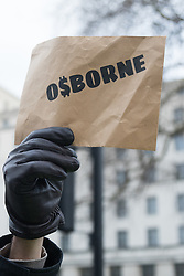 Whitehall, London, February 10th 2016. A protester's placard claims it is all about the money as an estimated 8,000 cabbies hold a go-slow in protest against what they say is unfair competition from minicab and Uber drivers who do not have to undergo the rigorous training and checks required for the licenced taxi trade. ///FOR LICENCING CONTACT: paul@pauldaveycreative.co.uk TEL:+44 (0) 7966 016 296 or +44 (0) 20 8969 6875. ©2015 Paul R Davey. All rights reserved.