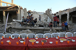 June 18, 2017 - Douma, Damascus, Syria - hildren  as they wait for Iftar, evening meal at the end of daily Ramadan fast at sunset, next to rubble and destroyed houses, which were damaged after air strikes, in Douma, Syria, 18 June 2017. Muslims around the world celebrate the holy month of Ramadan by praying during the night time and abstaining from eating, drinkin  (Credit Image: © Samer Bouidani/NurPhoto via ZUMA Press)
