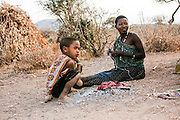 Hadzabe woman and Child, drying meat on a fire. Photographed in Tanzania, Lake Eyasi