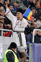 ROMANIA, Bucharest : Romania's fan dressed in national costume ring a bell during the Euro 2016 Group F qualifying football match Romania vs Northern Ireland in Bucharest, Romania on November 14, 2014.