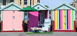 © Licensed to London News Pictures. 03/07/2018. Hove, UK. A woman sleeps in front of a colourful beach hut on the seafront at Hove, East Sussex on the south coast of England, as a heatwave continues across the UK. Photo credit: Ben Cawthra/LNP