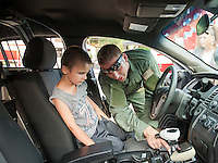 Belmont Special Operations Officer Kris Klootz shows Owen Bond the inside of his police car during Belmont PD's National Night Out Tuesday evening.  (Karen Bobotas/for the Laconia Daily Sun)