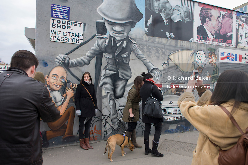 """Visitors enjoy the art on the old Berlin Wall at the East Side Gallery, the former border between Communist East and West Berlin during the Cold War. The Berlin Wall was a barrier constructed by the German Democratic Republic (GDR, East Germany) starting on 13 August 1961, that completely cut off (by land) West Berlin from surrounding East Germany and from East Berlin. The Eastern Bloc claimed that the wall was erected to protect its population from fascist elements conspiring to prevent the """"will of the people"""" in building a socialist state in East Germany. In practice, the Wall served to prevent the massive emigration and defection that marked Germany and the communist Eastern Bloc during the post-World War II period."""
