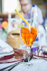 A glass with Aperol Spritz at restaurant table, Bavaria, Germany
