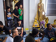 "07 MARCH 2015 - NAKHON CHAI SI, NAKHON PATHOM, THAILAND:  People watch the tattooing at the Wat Bang Phra tattoo festival. Wat Bang Phra is the best known ""Sak Yant"" tattoo temple in Thailand. It's located in Nakhon Pathom province, about 40 miles from Bangkok. The tattoos are given with hollow stainless steel needles and are thought to possess magical powers of protection. The tattoos, which are given by Buddhist monks, are popular with soldiers, policeman and gangsters, people who generally live in harm's way. The tattoo must be activated to remain powerful and the annual Wai Khru Ceremony (tattoo festival) at the temple draws thousands of devotees who come to the temple to activate or renew the tattoos. People go into trance like states and then assume the personality of their tattoo, so people with tiger tattoos assume the personality of a tiger, people with monkey tattoos take on the personality of a monkey and so on. In recent years the tattoo festival has become popular with tourists who make the trip to Nakorn Pathom province to see a side of ""exotic"" Thailand.  PHOTO BY JACK KURTZ"