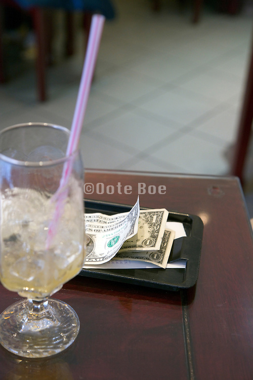 tip US three one dollar bills with empty glass and straw plus ice