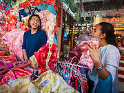 """03 FEBRUARY 2016 - BANGKOK, THAILAND:  Women shop for new traditional Chinese dresses before Chinese New Year in Bangkok. Thailand has the largest overseas Chinese population in the world; about 14 percent of Thais are of Chinese ancestry and some Chinese holidays, especially Chinese New Year, are widely celebrated in Thailand. Chinese New Year, also called Lunar New Year or Tet (in Vietnamese communities) starts Monday February 8. The coming year will be the """"Year of the Monkey.""""            PHOTO BY JACK KURTZ"""
