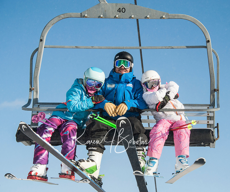 Jeff Thibault with two of his Camp 4 girls are all smiles as they head up the mountain on the Ramrod Quad for their All Mountain Base Camp Lesson on Wednesday morning.  (Karen Bobotas/for the Laconia Daily Sun)
