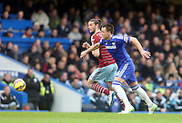 Chelsea's John Terry under pressure from  West Ham United's Andy Carroll<br /> <br /> Photographer Kieran Galvin/CameraSport<br /> <br /> Football - Barclays Premiership - Chelsea v West Ham United - Friday 26th December 2014 - Stamford Bridge - London<br /> <br /> © CameraSport - 43 Linden Ave. Countesthorpe. Leicester. England. LE8 5PG - Tel: +44 (0) 116 277 4147 - admin@camerasport.com - www.camerasport.com