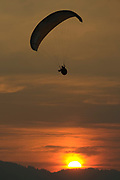 PRICE CHAMBERS / NEWS&GUIDE<br /> Jim Rooks swoops down past a smokey sunset Friday evening at the Jackson Hole High School football game. Rooks routinely delivers the game ball with his paraglider.
