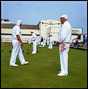 Mature men and women dressed in all-whites, playing bowls, Teignmouth Bowls club, Devon