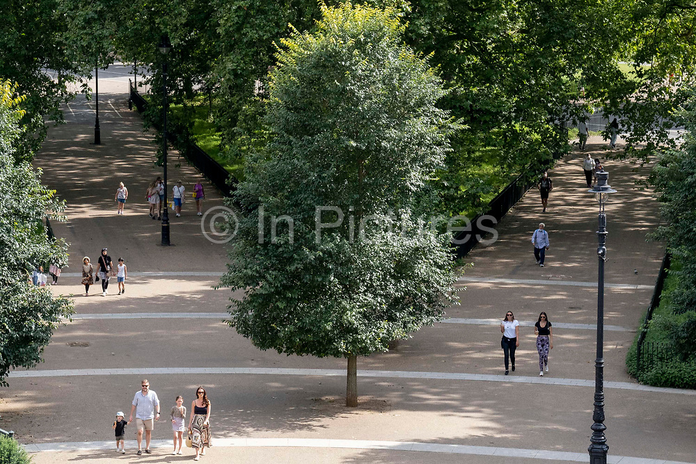 Seen from the elevation from the Marble Arch Mound, park users walk through  Speakers Corner at the north-eastern corner of Hyde Park, on 11th August 2021, in London, England.