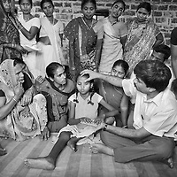 Dr. Yogesh Jain demostrates patient examination procedure on a young volunteer. Watching are some of the more than one hundred village health workers trained by the JSS who provide a frontline service. These health workers, all of them women, are selected by their home villages. They must be prepared to visit each and every household in their village regardless of caste of religion. <br /> <br /> The JSS (Jan Swasthya Sahyog or People's Health Support Group) is a public-health initiative established in 1996 by a handful of committed doctors, all of whom trained at elite medical schools in India. While many of their peers secured high profile, high earning posts in premier hospitals in India, the US and the UK, the doctors at JSS provide a service for poor and marginalised rural communities in Bilaspur district in the eastern India.<br /> <br /> The JSS operate out of a hospital in Ganiyari, near Bilaspur. Relying on grants and donations, the JSS provide a first-class service for a community that would otherwise rely on underfunded and poorly resourced government facilities. Though JSS hospital boasts 30 beds, two operating theatres, a fully-equipped lab and three outpatient clinics a week, the service provided by JSS is over-subscribed by a community of 800,000 people from 1,500 villages. <br /> <br /> To address the malnutrition, the JSS offers training on new agricultural techniques. The JSS has a well established outreach program of village-clinics and employs over 100 village health workers serving 53 villages. They also operate an ambulance service and assist with transport costs for a community who's access to essential services has been undermined by the Chhattisgarh government's decision to completely disinvest in public transport. <br /> <br /> Photo: Tom Pietrasik<br /> Chhattisgarh, India. <br /> March 2010