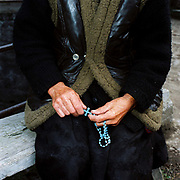An elderly Romanian woman sits on a wooden bench holding a cross on blue plastic rosary beads in her hands; Botiza, Maramures, Romania