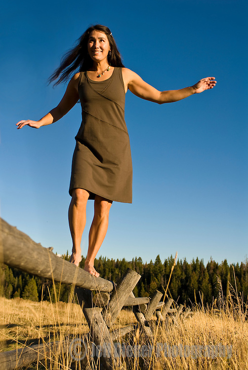 A young woman balances while walking a fence rail in Jackson Hole, Wyoming.