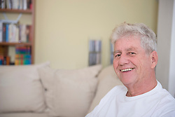Portrait of senior man sitting on couch, smiling