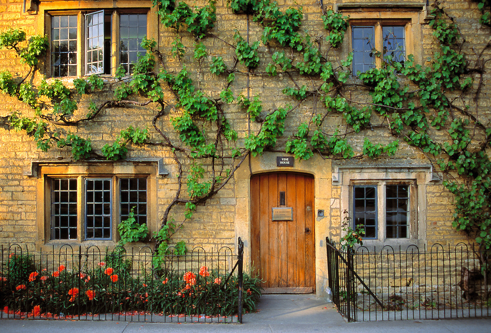 A vine-covered cottage greets visitors in Bourton-on-the-Water, Cotswolds, England.