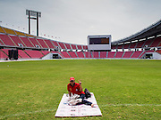 """19 NOVEMBER 2013 - BANGKOK, THAILAND: A Red Shirt protester sits by herself in Rajamangala Stadium before a Red Shirt political rally. As many as 30,000 """"Red Shirts"""" are expected in Bangkok this week ahead of a Thai court ruling that could cause the collapse of the government of Yingluck Shinawatra, the Prime Minister. The Red Shirts are gathering in a suburban sports stadium before marching to the court. The Red Shirts are mostly farmers and rural Thais who support the Shinawatra government.      PHOTO BY JACK KURTZ"""