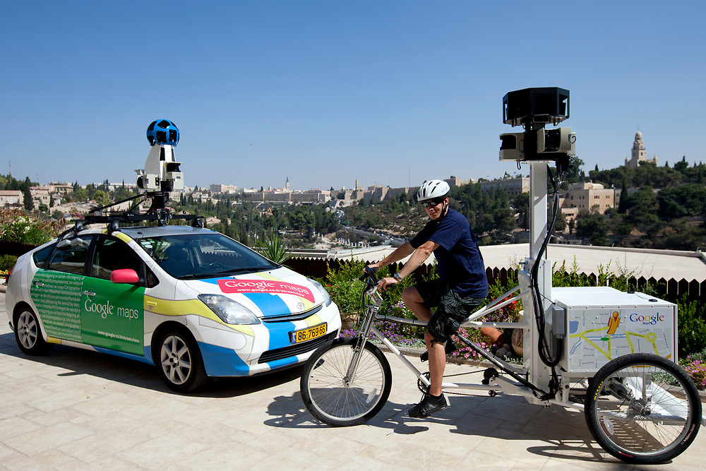 """A Google employee poses for photographers as a Street View car and a tricycle are displayed, following a press conference in Jerusalem, Israel, on September 12, 2011, in which Google has announced it will begin collecting images in Israel for the """"Street View"""" feature in Google Maps. In the coming weeks, Israel will join more than 30 other countries around the world which operate Street View, as Google cars and tricycles will begin driving and taking 360-degree photographs of streets, tourist destinations and other locations around the country. Images collected by the cameras mounted on vehicles will be processed and carefully stitched together to allow users to explore virtually and navigate cities, neighborhoods, streets and sites through panoramic street-level images."""