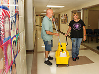 James Moussette and Addie Young waxing the floors of Elm Street School during preparations for the first day of school on September 4th for the Laconia School District.  (Karen Bobotas/for the Laconia Daily Sun)