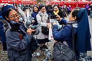 Op de Dam in Amsterdam voert een groep nonnen de duiven en gaat met de dieren op de foto.<br /> <br /> At the Dam Square in Amsterdam a group of nuns feed the pigeons and take pictures of them with the animals.