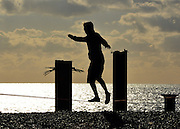 © Licensed to London News Pictures. 02/02/2013. Brighton, UK A man  learns how to tightrope. People enjoy the winter sun at Brighton sea front today 2nd February 2013. Photo credit : Stephen Simpson/LNP