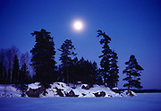 Full moon rising over Voyageur Island on a -30 degree Celsius January evening, Nym Lake, Quetico Provincial Park, Ontraio, Canada.