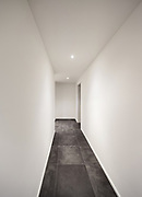 Architecture, modern entryway, long corridor with tiled floor black