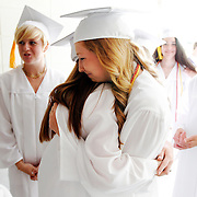 Beaufort Academy graduates Caroline Avera, left, and Miranda Weslake, right, embrace before walking in to the schools gymnasium for Commencement at Beaufort Academy on May 24, 2014.